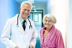 有年长女性微笑的医生 免版税库存照片