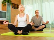 有年长的夫妇瑜伽在家 图库摄影