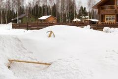 有黏附在随风飘飞的雪外面的轻拍的灵活的水管 免版税库存图片