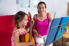 有年轻青春期前的女孩吉他教训在家 免版税库存图片