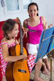 有年轻青春期前的女孩吉他教训在家 图库摄影
