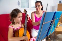 有年轻青春期前的女孩吉他教训在家 库存照片
