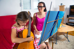 有年轻青春期前的女孩吉他教训在家 库存图片