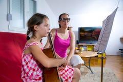 有年轻青春期前的女孩吉他教训在家 免版税库存照片