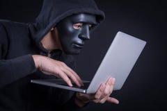 有黑面具运载的膝上型计算机的男性黑客 免版税库存图片