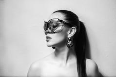 有黑鞋带面具的美丽的妇女在她的眼睛 红色性感的嘴唇和钉子特写镜头 库存照片