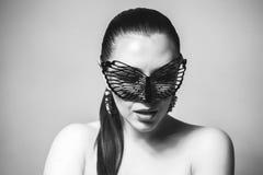 有黑鞋带面具的美丽的妇女在她的眼睛 红色性感的嘴唇和钉子特写镜头 免版税库存图片