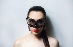有黑鞋带面具的美丽的妇女在她的眼睛 红色性感的嘴唇和钉子特写镜头 免版税库存照片