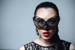 有黑鞋带面具的美丽的妇女在她的眼睛 红色性感的嘴唇和钉子特写镜头 免版税图库摄影