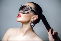 有黑鞋带面具的美丽的妇女在她的眼睛 红色性感的嘴唇和钉子特写镜头 图库摄影