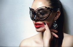 有黑鞋带面具的美丽的妇女在她的眼睛 红色性感的嘴唇和钉子特写镜头 库存图片
