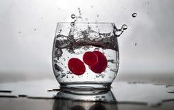 有水飞溅和新鲜的蕃茄的杯 图库摄影