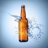 有水飞溅的啤酒瓶 免版税库存照片
