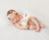 有头饰带和拿着的玩具睡觉的新出生的女孩 库存图片