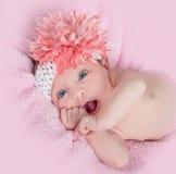 有头饰带和花的愉快的蓝眼睛的女婴 免版税图库摄影