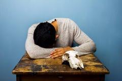 有头骨的哀伤的人在书桌 免版税库存照片