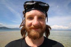 有兴高采烈的面孔的英俊的年轻人在潜航期间在海 库存照片
