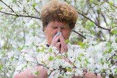 有鼻鼽的妇女在春天庭院里 免版税库存照片