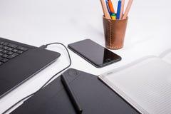 有黑便携式计算机的工作场所、笔记本、巧妙的电话、数字式图形输入板和笔和颜色笔和铅笔在白色ba 库存图片