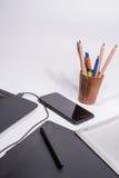 有黑便携式计算机的工作场所、笔记本、巧妙的电话、数字式图形输入板和笔和颜色笔和铅笔在白色ba 免版税库存照片