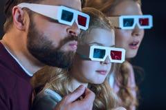 有戴3d眼镜和观看电影的一个孩子的家庭 免版税图库摄影