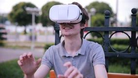 有3D VR头配显示器的年轻人在公园观看360部电影的,打VR比赛 股票视频