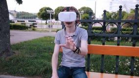 有3D VR头配显示器的年轻人在公园观看360部电影的,打VR比赛 股票录像