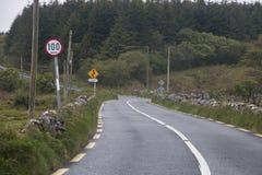 有100 km的典型的狭窄的爱尔兰乡下公路每个小时极限 库存照片