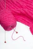 有2根针的桃红色线团在粉红色被编织的亚麻布 库存照片