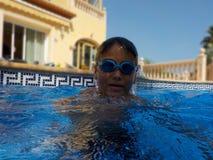 有a的一个男孩使用Google在游泳池的游泳 库存照片