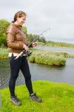 有a的年轻女渔翁乘坐了 库存照片