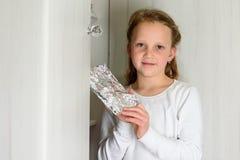 有Afikoman的女孩是残破的逾越节Seder matzah的半片断  免版税库存图片