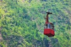 有Balea瀑布和绿色森林的缆车在Balea Cascada的背景中 库存图片