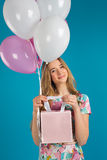 有baloons的甜女孩和一点prersents在蓝色背景的手上请求 免版税库存图片