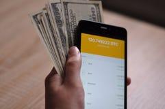 有bitcoin钱包的手在智能手机 免版税库存照片