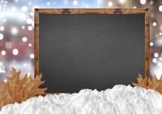 有blurr城市的空白的有雪的黑板和雪和叶子 库存照片