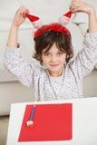 有Cardpaper的拿着圣诞老人的男孩和铅笔 免版税库存照片