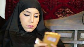 有chador头巾的妇女使用手机