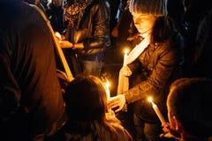 有childs的母亲在史特拉斯堡的中心点燃蜡烛 库存照片