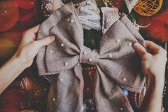 有Chrastmas手工制造麻袋布弓的手 免版税库存照片