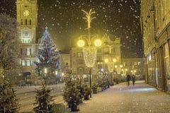 有Chrismas树和装饰的夜多雪的镇中心 免版税库存照片