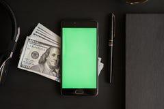 有chromakey的在一张黑织地不很细木桌上的智能手机锁上的和大模型与一百美元` s钞票 免版税库存图片
