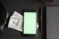有chromakey的在一张黑织地不很细木桌上的智能手机锁上的和大模型与一百美元` s钞票  图库摄影