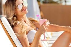 有coctail的少妇在海滩在夏天 免版税库存照片