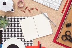 有coffe制造商和开放笔记本的办公桌 顶视图 图库摄影
