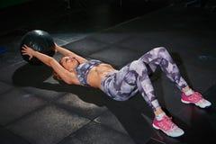 有crossfit球的,灰色砖墙美丽的肌肉适合妇女在背景中 十字架适合 免版税库存图片