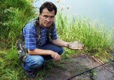 有crucian的渔夫在河Chagan 库存图片