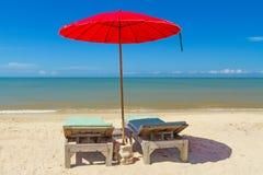 有deckchair的红色遮阳伞在热带海滩 库存照片