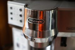 有Delonghi商标的热奶咖啡咖啡机 免版税图库摄影