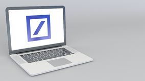 有Deutsche Bank AG商标的打开的和关闭的膝上型计算机 4K社论3D翻译 免版税库存照片